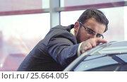 Купить «Young buyer inspects the car», видеоролик № 25664005, снято 21 января 2020 г. (c) Raev Denis / Фотобанк Лори