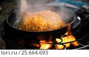 Купить «Chopped onions and carrots braised in a cast-iron skillet on an open fire. HD», видеоролик № 25664693, снято 27 февраля 2017 г. (c) ActionStore / Фотобанк Лори