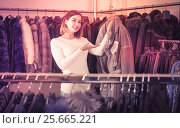 Купить «woman choosing sheepskin coat in women's cloths store», фото № 25665221, снято 23 февраля 2020 г. (c) Яков Филимонов / Фотобанк Лори