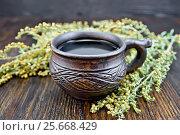 Купить «Чай с полынью в чашке на доске», фото № 25668429, снято 14 августа 2016 г. (c) Резеда Костылева / Фотобанк Лори