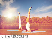 couple making yoga headstand on mat outdoors, фото № 25705845, снято 7 августа 2016 г. (c) Syda Productions / Фотобанк Лори