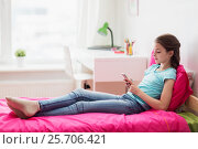 Купить «smiling girl texting on smartphone at home», фото № 25706421, снято 5 ноября 2016 г. (c) Syda Productions / Фотобанк Лори