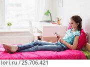 Купить «smiling girl texting on smartphone at home», фото № 25706421, снято 5 ноября 2016 г. (c) Syda Productions / Фотобанк Лори