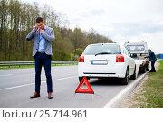 Купить «Man calling while tow truck picking up his broken car», фото № 25714961, снято 24 апреля 2018 г. (c) Andrejs Pidjass / Фотобанк Лори