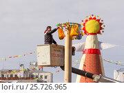 Купить «Мужчина вешает подарки на масленичный столб. Самара», фото № 25726965, снято 26 февраля 2017 г. (c) Акиньшин Владимир / Фотобанк Лори