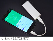 Купить «Смартфон заряжается от внешнего аккумулятора», эксклюзивное фото № 25729877, снято 11 марта 2017 г. (c) Dmitry29 / Фотобанк Лори