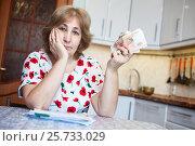 Купить «Грустная пенсионерка показывает деньги, сидит за кухонным столом со счетами на оплату», фото № 25733029, снято 6 ноября 2016 г. (c) Кекяляйнен Андрей / Фотобанк Лори