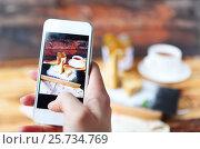 Купить «Woman taking a photo of Traditional Hungarian Esterhazy cake with smartphone», фото № 25734769, снято 6 марта 2016 г. (c) Дарья Петренко / Фотобанк Лори