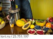 Купить «Shop assistant preparing papaya juice», фото № 25751197, снято 4 октября 2016 г. (c) Wavebreak Media / Фотобанк Лори