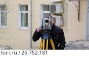 Купить «Геодезист стоит за электронным прибором и выполняет измерения в поле», видеоролик № 25752181, снято 14 марта 2017 г. (c) Александр Фрейдин / Фотобанк Лори