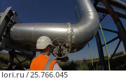 The engineer opens and closes the valve on the industrial pipeline for hot water and heating, gas, oil, resources. Стоковое видео, видеограф Mikhail Erguine / Фотобанк Лори