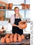 Купить «Portrait of glad woman pottery worker with ceramic crockery», фото № 25772361, снято 17 июля 2019 г. (c) Яков Филимонов / Фотобанк Лори