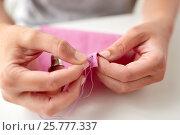 Купить «woman with needle stitching fabric pieces», фото № 25777337, снято 29 сентября 2016 г. (c) Syda Productions / Фотобанк Лори