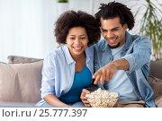 Купить «smiling couple with popcorn watching tv at home», фото № 25777397, снято 17 декабря 2016 г. (c) Syda Productions / Фотобанк Лори