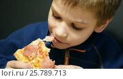 Cute boy eating pizza. Стоковое видео, видеограф Сергей Кальсин / Фотобанк Лори