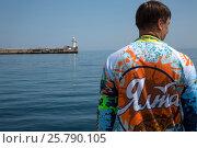 Купить «Мужчина в толстовке Ялтинского рыболовного клуба  смотрит на Черное море с набережной города Ялты, Республика Крым», эксклюзивное фото № 25790105, снято 7 мая 2016 г. (c) Николай Винокуров / Фотобанк Лори