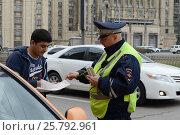 Купить «Инспектор ДПС проверяет документы у водителя такси в центре Москвы», фото № 25792961, снято 9 апреля 2016 г. (c) Free Wind / Фотобанк Лори