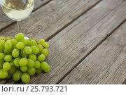 Купить «Close-up of green bunch of grapes with glass of wine», фото № 25793721, снято 19 декабря 2016 г. (c) Wavebreak Media / Фотобанк Лори