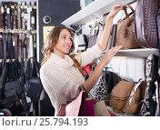 Купить «Positive young woman selecting new handbag», фото № 25794193, снято 21 октября 2018 г. (c) Яков Филимонов / Фотобанк Лори