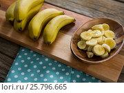 Banana and slices of banana in plate kept on chopping board. Стоковое фото, агентство Wavebreak Media / Фотобанк Лори