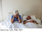 Senior woman getting disturbed with man snoring on bed. Стоковое фото, агентство Wavebreak Media / Фотобанк Лори