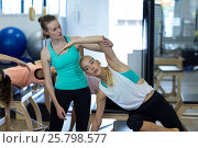 Купить «Female trainer assisting woman with exercise», фото № 25798577, снято 7 октября 2016 г. (c) Wavebreak Media / Фотобанк Лори