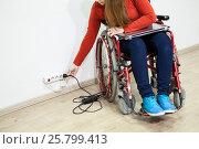 Купить «Женщина инвалид тянется к электрической розетке в стене для включение ноутбука», фото № 25799413, снято 4 декабря 2015 г. (c) Кекяляйнен Андрей / Фотобанк Лори