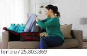 Купить «woman packing clothes to travel bag at home», видеоролик № 25803869, снято 19 января 2017 г. (c) Syda Productions / Фотобанк Лори