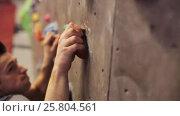 Купить «young man exercising at indoor climbing gym wall», видеоролик № 25804561, снято 2 марта 2017 г. (c) Syda Productions / Фотобанк Лори