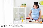 Купить «pregnant woman chopping fruits at home kitchen», видеоролик № 25804609, снято 16 марта 2017 г. (c) Syda Productions / Фотобанк Лори