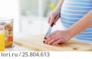 Купить «pregnant woman chopping fruits at home kitchen», видеоролик № 25804613, снято 16 марта 2017 г. (c) Syda Productions / Фотобанк Лори