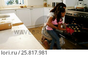 Купить «Mother and daughter removing tray of cookies from oven in kitchen», видеоролик № 25817981, снято 28 марта 2020 г. (c) Wavebreak Media / Фотобанк Лори