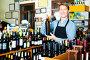 Male seller with wine bottle in hands, фото № 25820153, снято 27 марта 2017 г. (c) Яков Филимонов / Фотобанк Лори