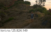 Купить «Cheering young woman backpacker at sunrise seaside mountain peak», видеоролик № 25824149, снято 18 марта 2017 г. (c) Valentyn Kondratiuk / Фотобанк Лори