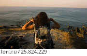 Купить «Cheering young woman backpacker at sunrise seaside mountain peak», видеоролик № 25824229, снято 1 февраля 2017 г. (c) Valentyn Kondratiuk / Фотобанк Лори