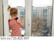 Маленькая девочка стоит на подоконнике высотного дома. Опасность. Стоковое фото, фотограф Акиньшин Владимир / Фотобанк Лори