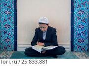 Мальчик читает священную книгу мусульман Коран в молельном зале Московской соборной мечети, Россия (2017 год). Редакционное фото, фотограф Николай Винокуров / Фотобанк Лори