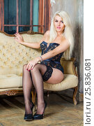 Купить «Young blonde woman in black lingerie and shoes sits on sofa near lattice window in room», фото № 25836081, снято 17 сентября 2015 г. (c) Losevsky Pavel / Фотобанк Лори