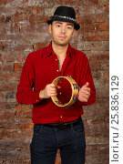 Купить «Handsome man in hat poses with tambourine in studio with brick wall», фото № 25836129, снято 9 февраля 2016 г. (c) Losevsky Pavel / Фотобанк Лори