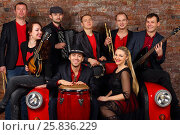 Купить «Music brass band of eight young people in red and black clothes pose in studio with car couch», фото № 25836229, снято 9 февраля 2016 г. (c) Losevsky Pavel / Фотобанк Лори