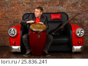 Купить «Handsome young man hits drums on sofa car with guitar in studio with brick wall», фото № 25836241, снято 9 февраля 2016 г. (c) Losevsky Pavel / Фотобанк Лори