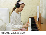 Teen girl playing on synthesizer melody, put headphones on her head. Стоковое фото, фотограф Losevsky Pavel / Фотобанк Лори