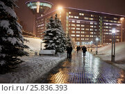 RUSSIA, KRASNOGORSK - DEC 12, 2014: People walk in winter evening near complex of the House of Moscow Oblast Government. Construction of House was started in 2004 and ended in 2007. Редакционное фото, фотограф Losevsky Pavel / Фотобанк Лори