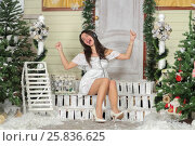 Купить «Full portrait of young woman sitting on threshold of fake home and listening music in headphone and dance sitting. Christmas interior studio», фото № 25836625, снято 14 декабря 2014 г. (c) Losevsky Pavel / Фотобанк Лори