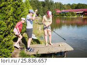 Купить «Mother and two children fishing at pond on sunny day», фото № 25836657, снято 25 июля 2015 г. (c) Losevsky Pavel / Фотобанк Лори