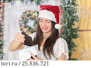 Купить «Lovely woman with elegant style in Santa cap standing near door of house sham and holding large bar of chocolate, read label on packaging», фото № 25836721, снято 14 декабря 2014 г. (c) Losevsky Pavel / Фотобанк Лори