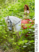 Купить «Red-haired young woman in red dress sits on white horse among green plants in park», фото № 25836789, снято 20 сентября 2015 г. (c) Losevsky Pavel / Фотобанк Лори