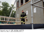 Купить «MOSCOW, RUSSIA - AUG 20, 2016: Firefighter stand next to the dummy building during the Moscow City Championship of combat deployment in Luzhniki», фото № 25836877, снято 20 августа 2016 г. (c) Losevsky Pavel / Фотобанк Лори
