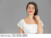 Купить «Half-length portrait of woman in white dress looking at us and smile, on gray background», фото № 25836885, снято 14 декабря 2014 г. (c) Losevsky Pavel / Фотобанк Лори