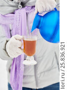 Купить «Female hands in white knitted gloves pour hot beverage into glass cup outdoor», фото № 25836921, снято 25 января 2015 г. (c) Losevsky Pavel / Фотобанк Лори